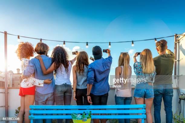 Vista posterior de amigos juntos de pie en la terraza