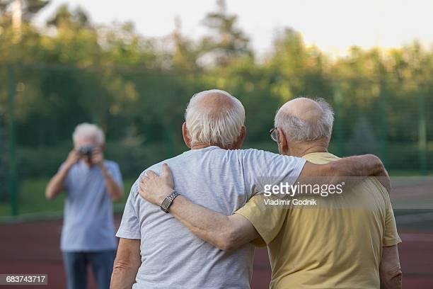 rear view of friends standing with arm around while man photographing in background - amigos abrazados espaldas fotografías e imágenes de stock