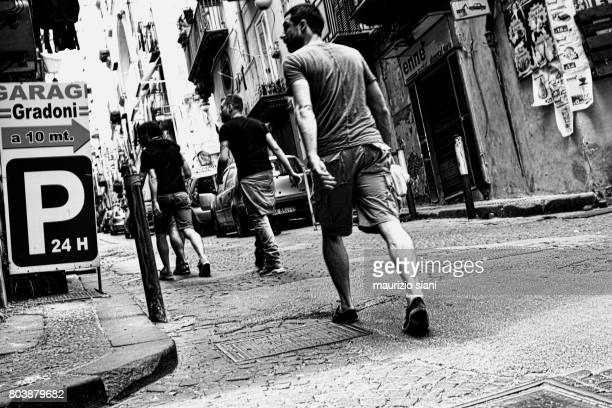 rear view of friends walking down the streets of naples (italy) - centro storico foto e immagini stock