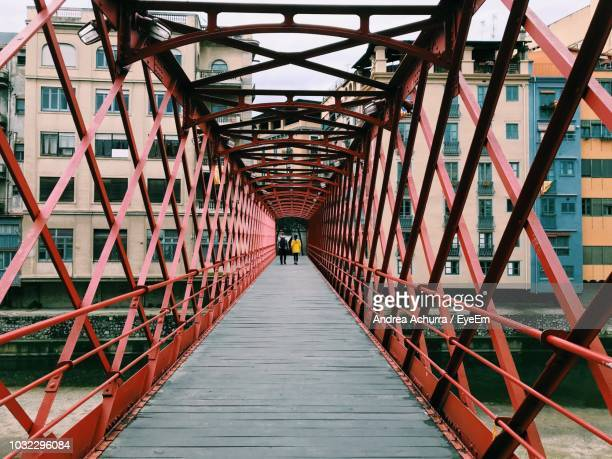 rear view of friends walking on footbridge in city - footbridge stock photos and pictures