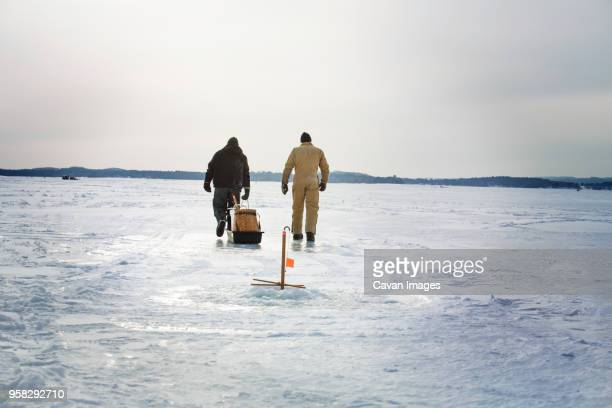 Rear view of friends walking on frozen lake against cloudy sky