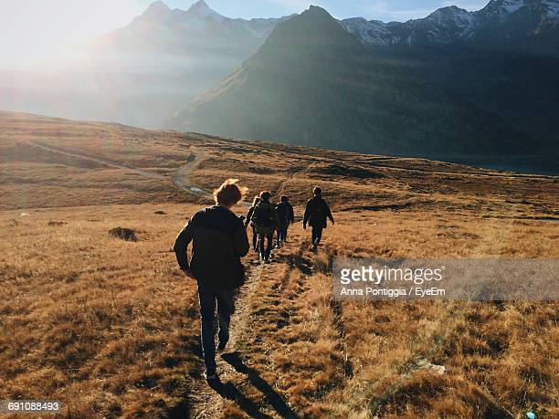Rear View Of Friends Walking On Grassy Field Against Mountains