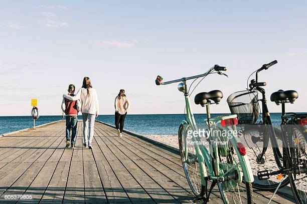 Rear view of friends walking on pier with bicycles in foreground at beach