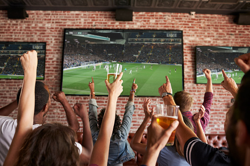 Rear View Of Friends Watching Game In Sports Bar On Screens 679271216