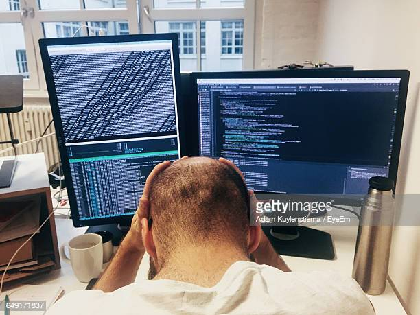 Rear View Of Frustrated Programmer With Head In Hands At Desk
