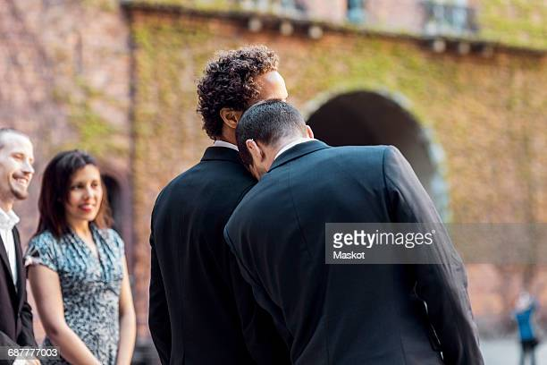 Rear view of gay man leaning on partners shoulder during wedding ceremony