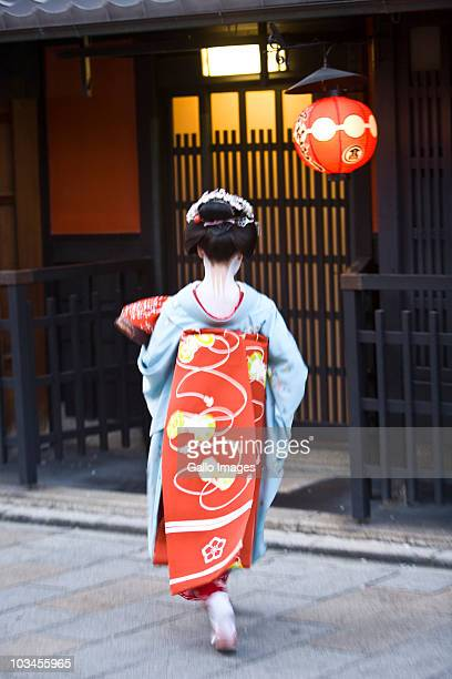 Rear view of Geisha in kimono walking by restaurants on Pontocho, a pedestrian-only street in Gion district, Kyoto, Honshu island, Japan