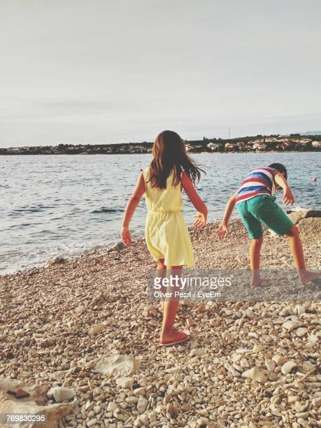 Rear View Of Girl And Boy Playing At Beach Against Sky