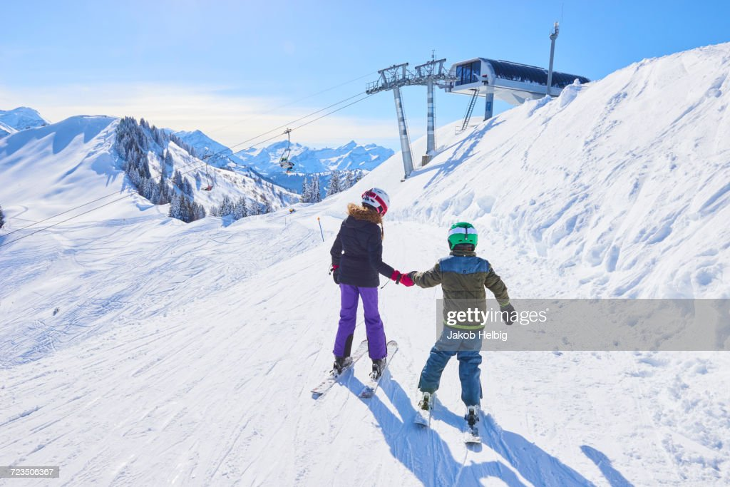 Rear view of girl and brother holding hands on ski slope, Gstaad, Switzerland : Stock Photo