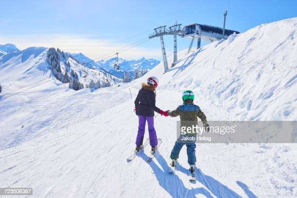 rear view of girl and brother holding hands on ski slope, gstaad, switzerland - グスタード ストックフォトと画像