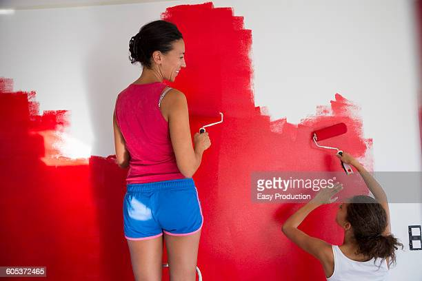 Rear view of girl and mother painting red wall with paint rollers