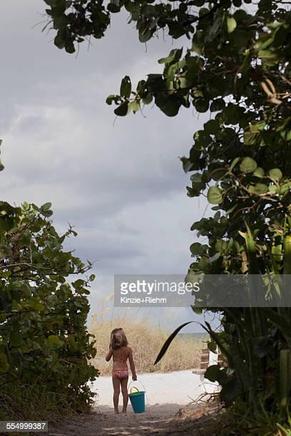 Rear view of girl carrying bucket walking along woodland beach path, Anna Maria Island, Florida, USA