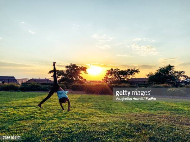 rear view of girl doing cartwheel on grassy field at park against sky during sunset - cartwheel stock pictures, royalty-free photos & images