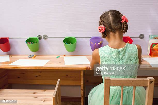Rear view of girl drawing at desk in classroom