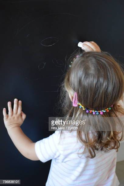Rear View Of Girl Drawing With Chalk On Blackboard