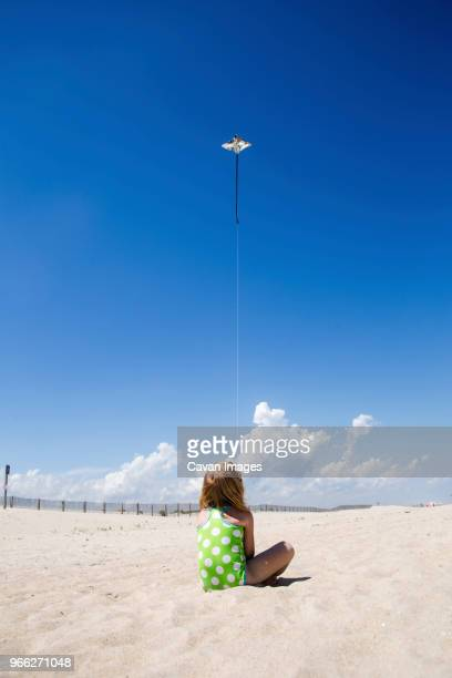 rear view of girl flying kite while sitting at beach during sunny day - westminster maryland stock pictures, royalty-free photos & images
