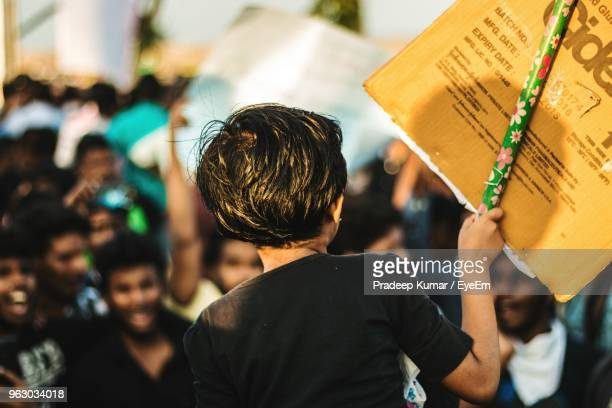 rear view of girl holding banner during protest - protestor stock pictures, royalty-free photos & images