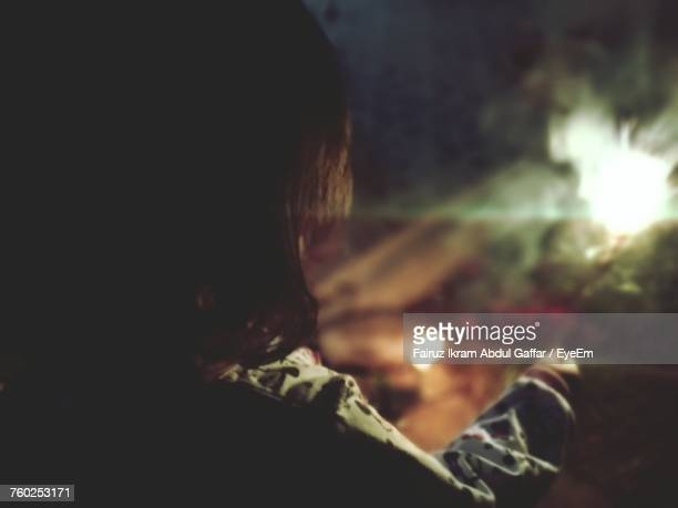 Rear View Of Girl Holding Burning Sparkler At Night