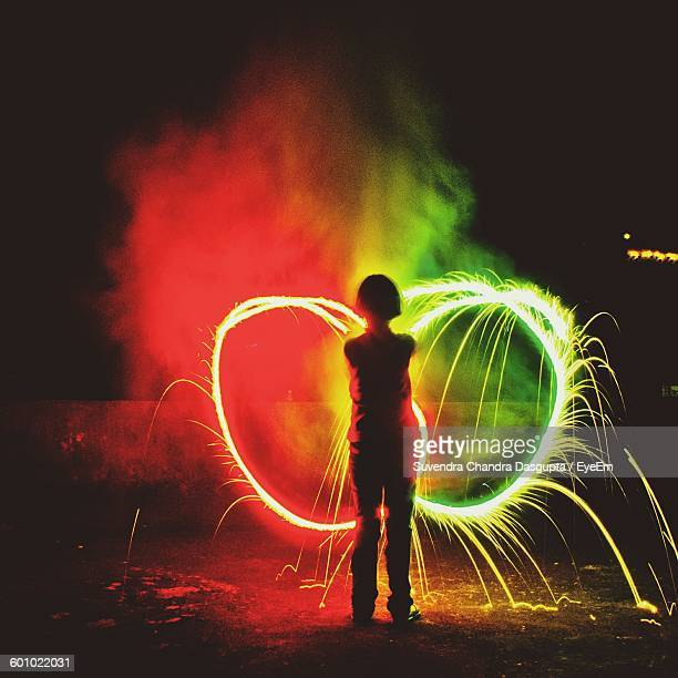 Rear View Of Girl Holding Sparkler At Night During Diwali