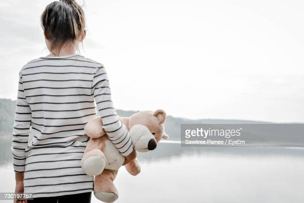 Rear View Of Girl Holding Teddy Bear While Standing Against River