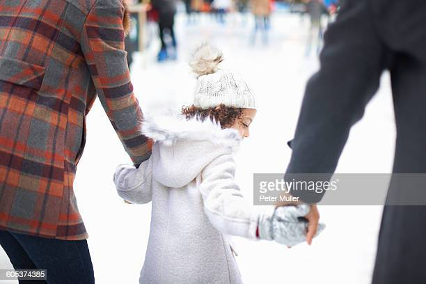 Rear view of girl ice skating with parents, holding hands