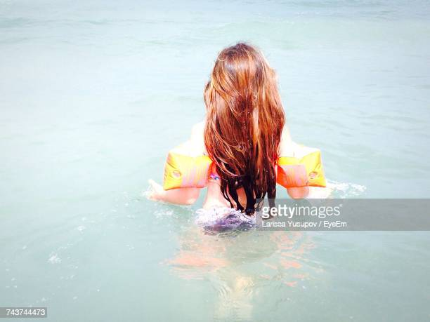 rear view of girl in sea - armband stock pictures, royalty-free photos & images