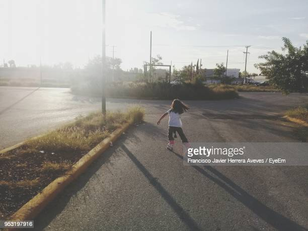 Rear View Of Girl Inline Skating On Road During Sunset