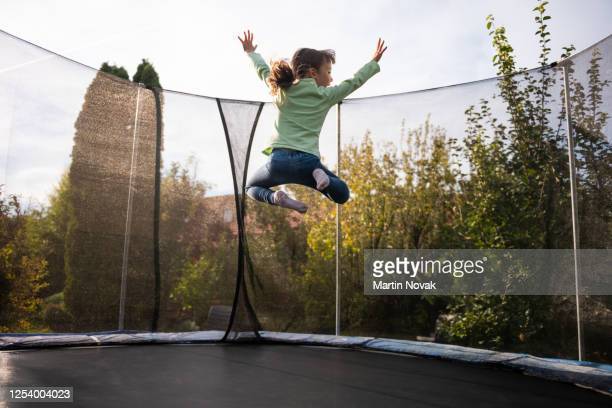rear view of girl jumping high on trampoline - fanny stock pictures, royalty-free photos & images