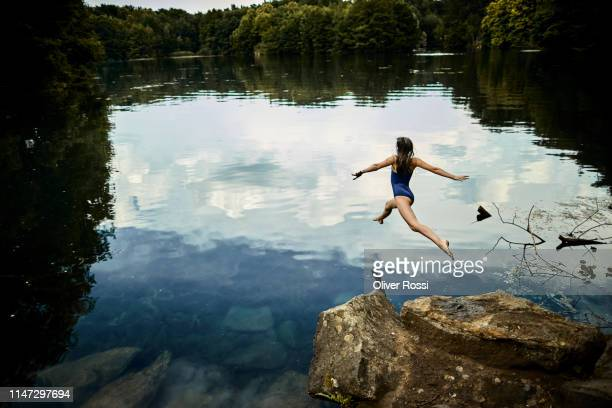 rear view of girl jumping into a lake - mut stock-fotos und bilder