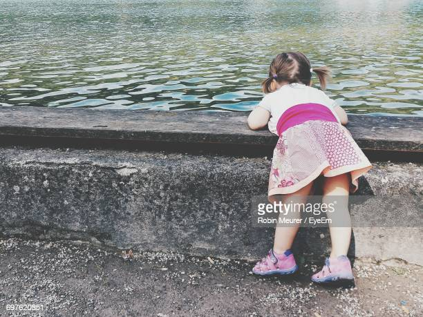 Rear View Of Girl Leaning On Retaining Wall By Pond