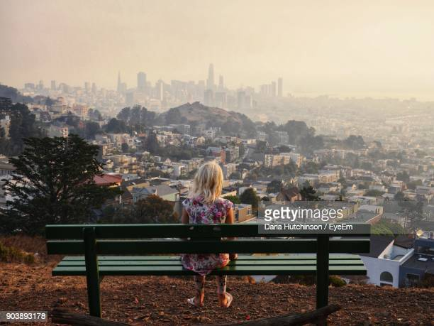 rear view of girl looking at cityscape while sitting on bench against clear sky - air pollution stock pictures, royalty-free photos & images