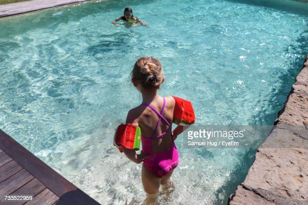 Rear View Of Girl Looking At Friend Swimming In Pool