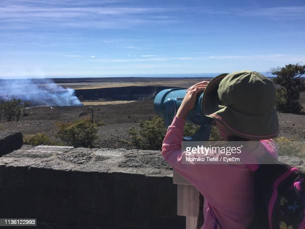 Rear View Of Girl Looking At Landscape Through Telescope