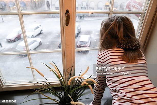 Rear View Of Girl Looking At Snow Covered Cars On Road Through Window