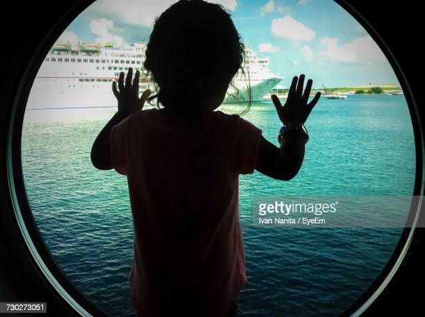 Rear View Of Girl Looking Through Circular Window Of Boat