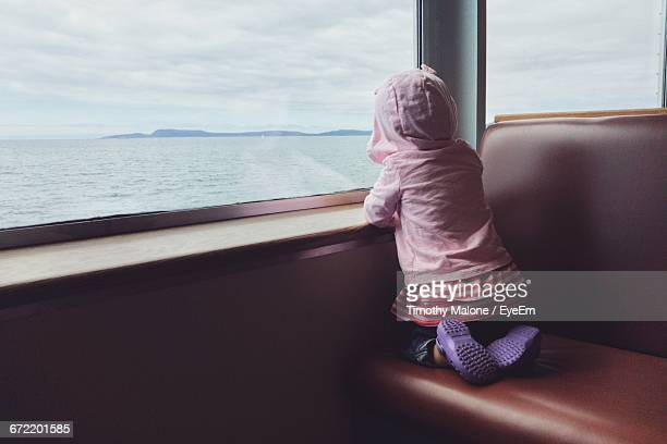 rear view of girl looking through ferry window while wearing hooded shirt - ferry photos et images de collection