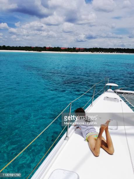 Rear View Of Girl Lying On Boat In Sea Against Cloudy Sky