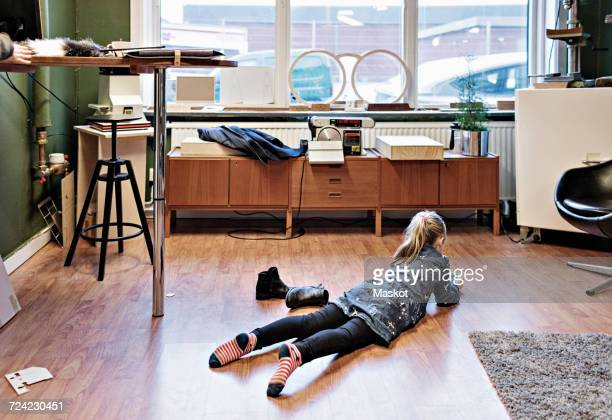 rear view of girl lying on hardwood floor at eyeglasses workshop - girls in socks stock photos and pictures