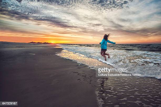 Rear view of girl on beach at sunrise jumping in mid air