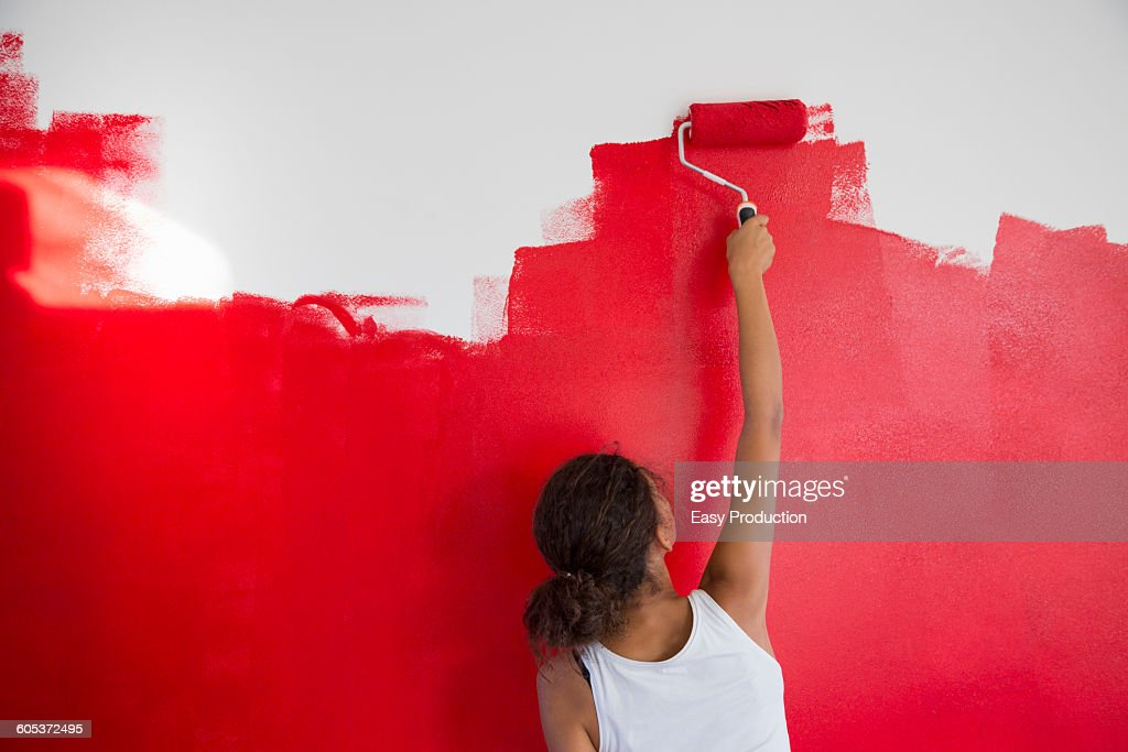 Rear view of girl painting red wall with paint roller : Stock Photo