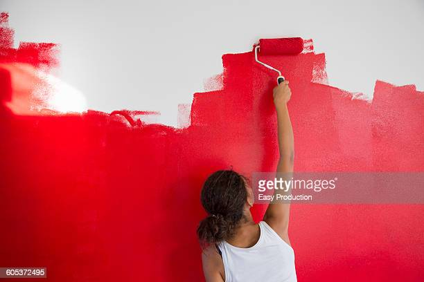 rear view of girl painting red wall with paint roller - home improvement stock pictures, royalty-free photos & images