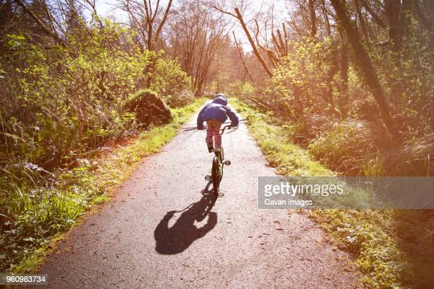 Rear view of girl performing stunt while riding bicycle on street during sunny day