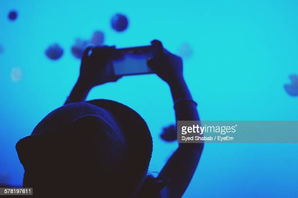 Rear View Of Girl Photographing Jellyfish In Aquarium