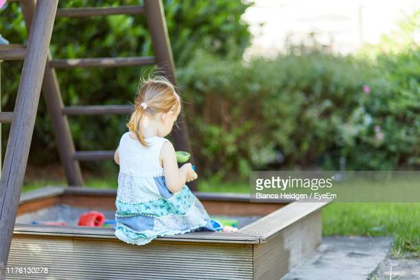rear view of girl playing in sandbox at park - 2 girls 1 sandbox stock photos and pictures