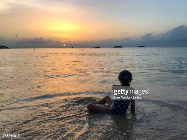 Rear View Of Girl Playing In Sea Against Sky During Sunset