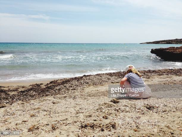 Rear View Of Girl Playing On Shore At Beach Against Sky