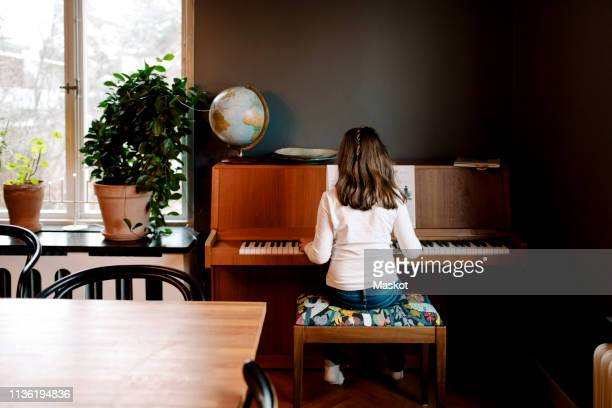 rear view of girl playing piano while sitting in living room at home - instrumento musical - fotografias e filmes do acervo