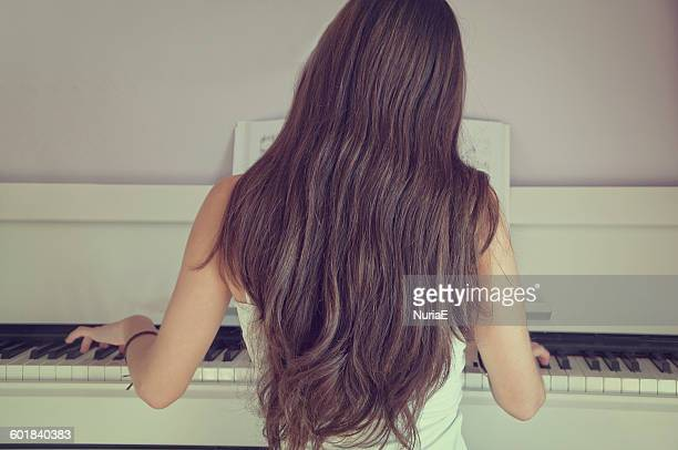 Rear view of girl playing the piano