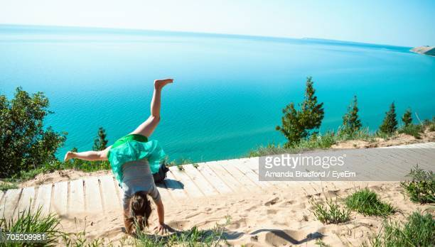 Rear View Of Girl Practicing Cartwheel At Shore Of Lake Michigan