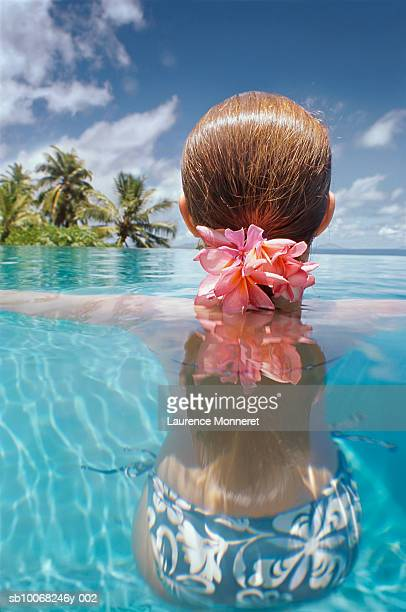 Rear view of girl (12-13) relaxing in swimming pool, surface level view